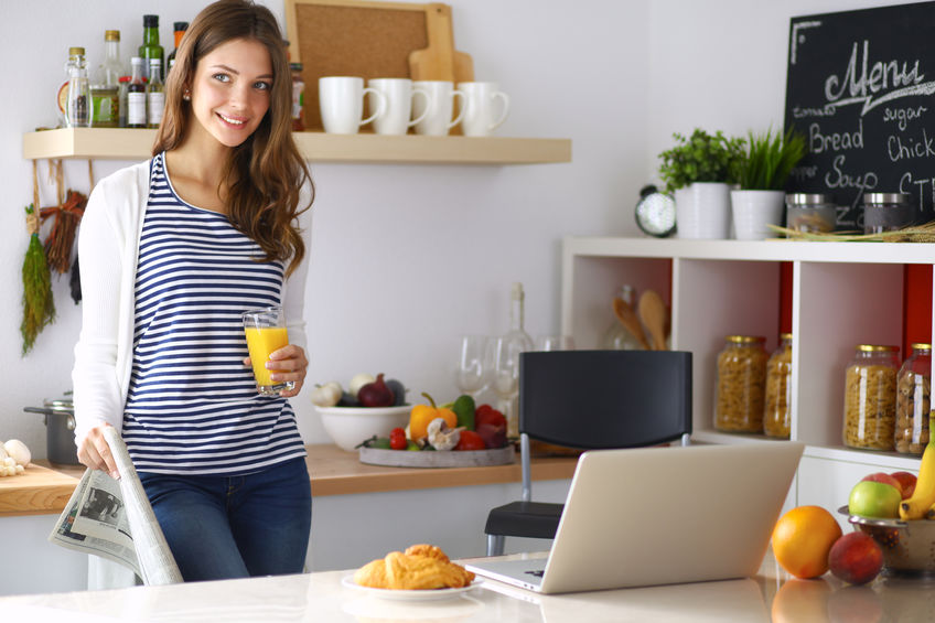 Woman in kitchen with glass of orange juice in hand on laptop at table