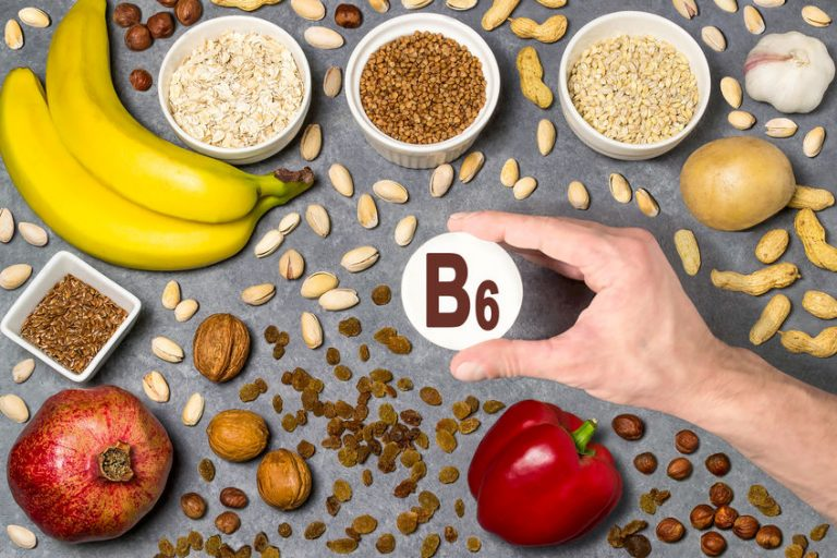 Food rich in vitamin B6. Various natural sources of vitamins. Useful food for health and balanced diet. Prevention of avitaminosis. Man's hand holds tag with name of vitamin B6. Top view