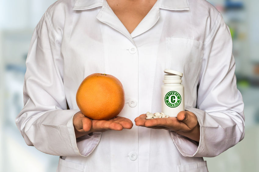 female doctor holding an orange in her right hand and a bottle of vitamin C in her left hand