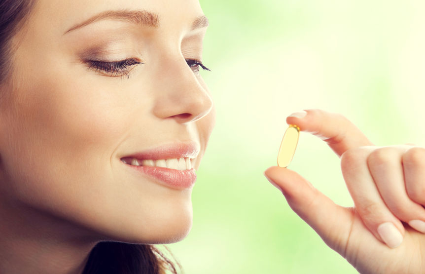 Woman showing Omega 3 fish oil capsule