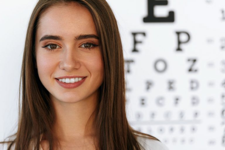 Beautiful Woman With Visual Eye Test Chart On Background