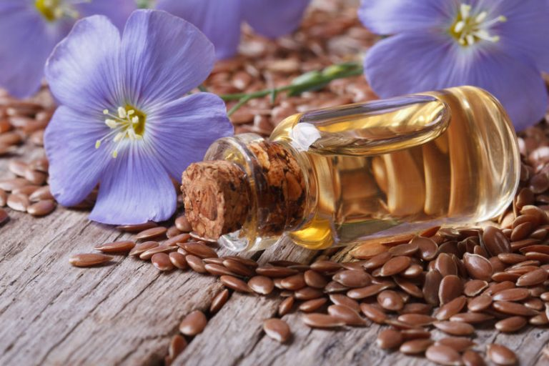flax seeds, blue flowers and oil close-up horizontal