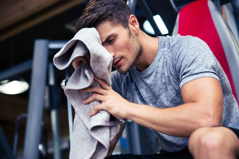 Man sitting on the bench with towel
